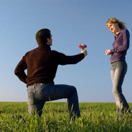 Man Holding Flowers Down On One Knee In Front Of Woman