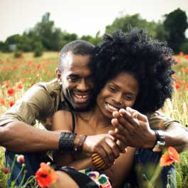 Couple Embracing In Field Of Flowers