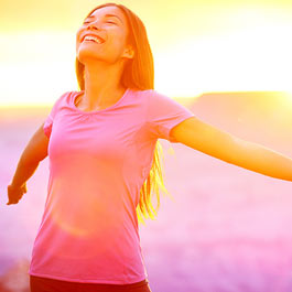 Woman happy with arms stretched out and sun beaming down