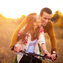 Woman gives man a peck will riding together on a bike