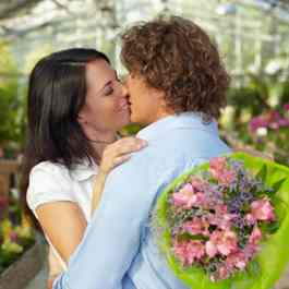 Couple kissing holding flowers
